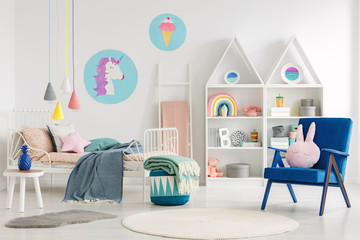 Sweet bedroom interior for a kid with a blue armchair, rabbit pillow, bed, unicorn and ice cream posters and shelves
