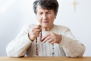 Focused grandmother in melancholy praying with red rosary in the church