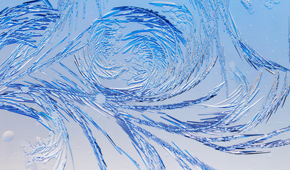 Blue drawings on the glass in the frost