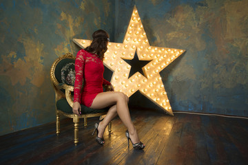 A sexy girl with red lips in a luxurious red dress and high heels sits in chair in a rich studio interior with gold and a light star