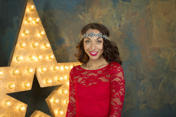 A sexy smiling girl with red lips in a luxurious red dress and high heels in a rich studio interior with gold and a light star