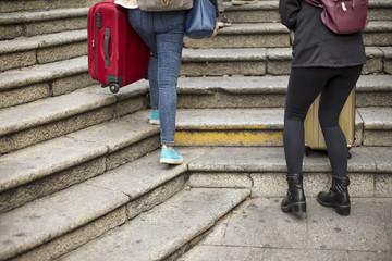 dettaglio del trolley di  due viaggiatrice che con fatica provano a trasportare le loro valige in una scalinata