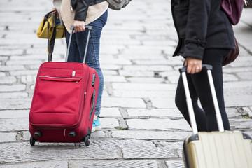 dettaglio del trolley di due viaggiatrice che si spostano in una città