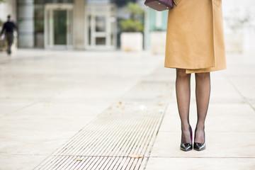 Dettaglio di gambe gonna e scarpe con il tacco