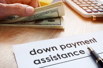 Down payment assistance form and dollar banknotes.