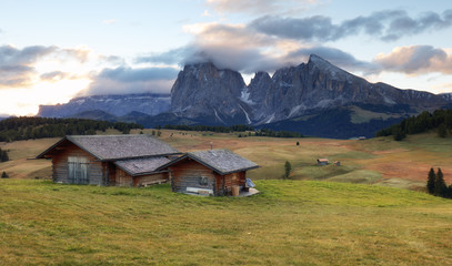 Beautiful Scenery from Alpe di Siusi, Italy in summer sunrise light with small wooden cottage and sharp mountains of dolomite. Seiser Alm with Langkofel Group South Tyrol, Italy