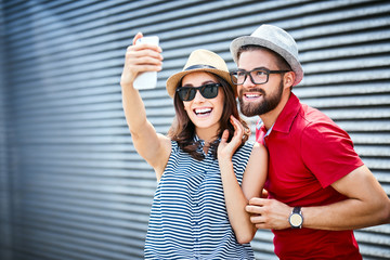 Young couple smiling and taking selfie outdoors