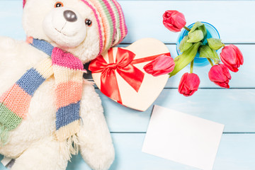Colorful red spring tulip flowers in nice blue vase, blank photo frame and stuffed toy teddy bear with decorative heart on light wooden background as greeting card