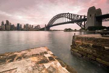 The iconic Sydney Harbour Bridge (also called 'the coat hanger') on an overcast day.  The bridge was completed and opened in 1932.  It carries rail, vehicular, bicycle, and pedestrian traffic.