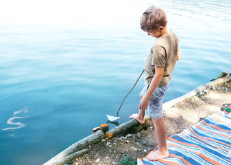 Boy launch paper boat in lake water
