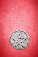 Wiccan and witchcraft pentagram on a textured red background with space for copy and text