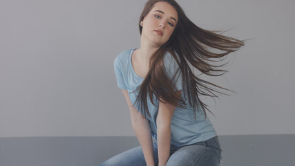 closeup portrait of young wooman posing to a camera with blowed out hair on grey