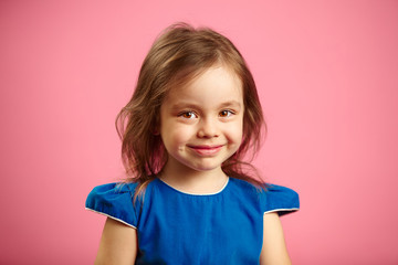 portrait of beautiful child girl with charming look on isolated blue background.