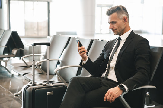 Handsome mature businessman using mobile phone