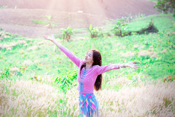 beautiful asia girl alone playing in meadow at sunset time