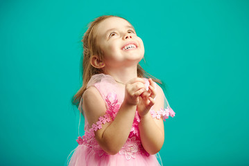 Surprised little girl in beautiful pink dress clasped hands in front of her and looks up happily, isolated portrait on blue background.