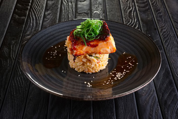 Roasted salmon with rice and spices decorated with seaweed