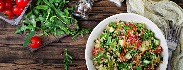 Salads with quinoa,  arugula, radish, tomatoes and cucumber in bowl on  wooden background.  Healthy food, diet, detox and vegetarian concept. Top view. Flat lay