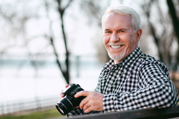 Improve your skills. Merry mature man utilizing camera and grinning to camera
