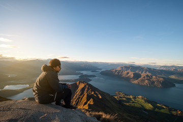 A young Asian man enjoying looking at the stunning scenery on the high mountain before sunset.