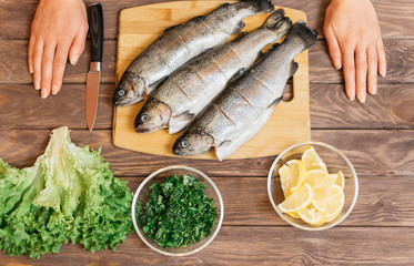 Woman will cook fish on wooden table.