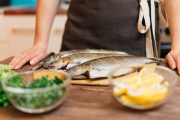 Woman will cook fish dish in kitchen.