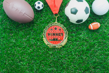 Table top view aerial image soccer or football tournament season background.Flat lay objects gold medal & ball on the artificial green grass wallpaper.Copy space for creative design mock up text.