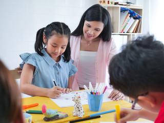 Close up Teacher and the littel asian girl in art class.