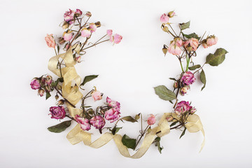 Wreath of dried flowers with a gold ribbon on a white wooden board background. Top view