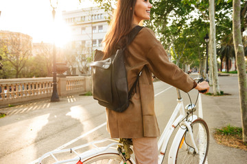 Back view image of young lady on bicycle on the street.