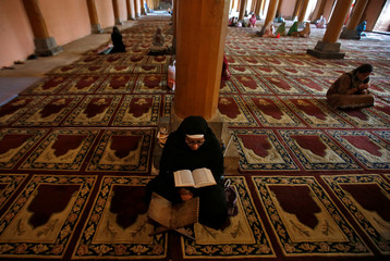 A Muslim woman reads the Koran inside Jamia Masjid during the holy month of Ramadan in Srinagar