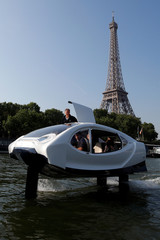 The Bubbles water taxi flies above the surface of the Seine River near the Eiffel Tower during a demonstration by the SeaBubbles company in Paris