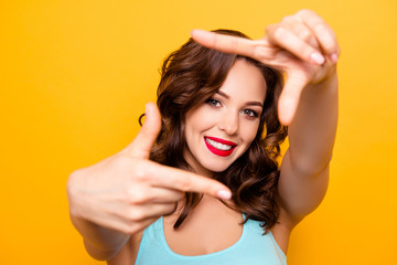 Portrait of pretty creative girl with beaming smile red pomade lipstick making frame with thumbs and forefingers looking at camera isolated on yellow background