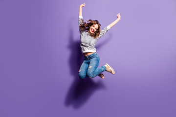 Portrait of cheerful positive girl jumping in the air with raised fists looking at camera isolated on violet background. Life people energy concept Wall mural