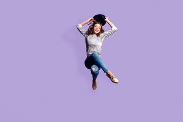 Portrait of funny comic girl sitting in the air holding hat in hands looking at camera cool jumper isolated on violet background