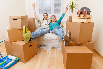 Photo of couple sitting on couch among cardboard boxes
