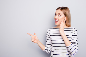 Portrait with copy space for advertisement of attractive, amazed, stylish, impressed, funny girl with open mouth holding palm near face pointing forefinger to empty place isolated on grey background