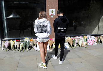 People wearing Ariana Grande sweatshirts look at tributes left in St Anne's Square on the first anniversary of the Manchester Arena bombing, in Manchester
