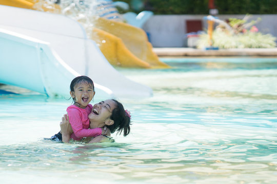 mother and daughter swiming in water park
