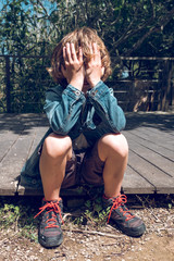 Little boy sitting bridge with hands over his face