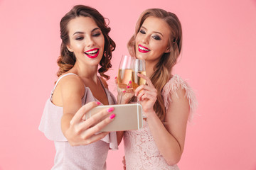 Photo of two young party women smiling and taking selfie photo on smartphone while holding glasses with champagne, isolated over pink background