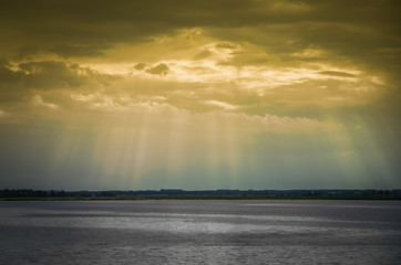 Sun rays penetratinging through the clouds over the lake.