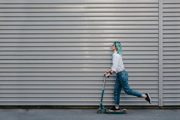 Young urban woman in jeans with blue hair riding a kick scooter against the wall Wall mural