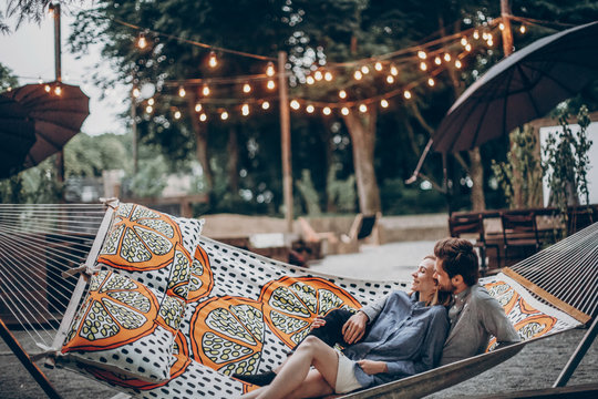 stylish hipster family cuddling and relaxing in hammock under retro lights in evening summer park. rustic man and woman embracing and resting in forest. space for text. atmospheric moment