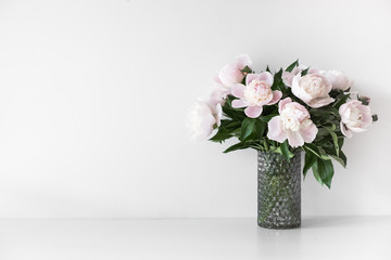 Bouquet of tender pink peonies in vase near white wall