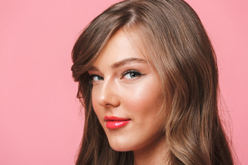 Image closeup of young european woman 20s with long curly hairstyle and evening makeup smiling at camera with seductive look, isolated over pink background