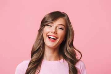 Image closeup of cheerful european woman 20s with long curly hairstyle and evening makeup laughing while looking at you with happy look, isolated over pink background