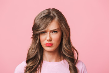 Photo closeup of upset woman with long curly hair in basic t-shirt pouting and frowning in resentment, isolated over pink background