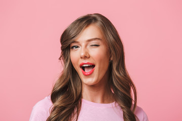 Image closeup of young attractive woman 20s with long curly hairstyle and seductive look winking at camera with smile, isolated over pink background