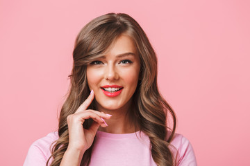 Closeup photo of adorable content woman with long curly brown hair smiling while looking at you, isolated over pink background